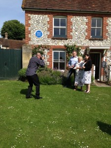 """L to R:  James Lovegrove, Author of """"Sherlock Holmes Gods of War""""; Eastbourne Borough Council Cabinet Member for Tourism, Leisure & Sports Services, Cllr Carolyn Heaps; and Sarah Leighton of the Beachy Head Estate at the launch of the new Sherlock Holmes book.  The launch took place on East Dean village green in front of the blue plaque on the wall of the Beachy Head Estate Office honouring the celebrated detective."""